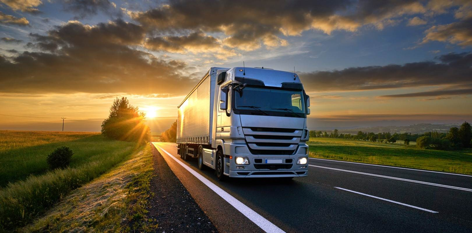 Haulage vehicle driving through countryside at sunset